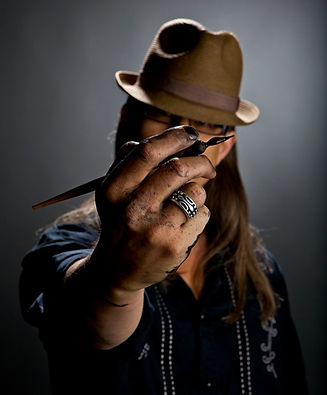Graham Smith, artist, illustrator, headshot 1, holding a pen in front of his face, wearing a hat with inky hands.