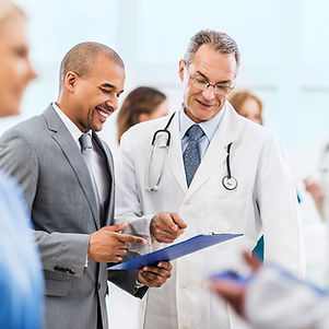 businessman having discussion with older male doctor