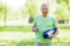 Healthy smiling older man with yoga mat and water bottle