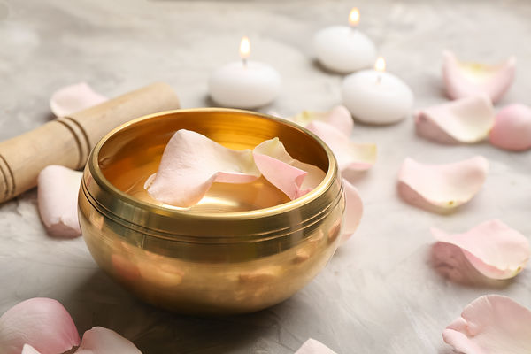 Golden singing bowl with petals and mallet on grey table, closeup. Sound healing.jpg