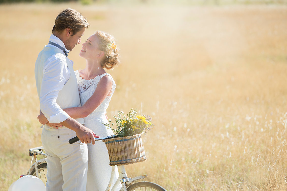 A couple in love in a field on a bicycle