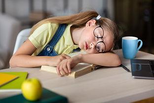 tired-school-girl-in-glasses-sleeping-at