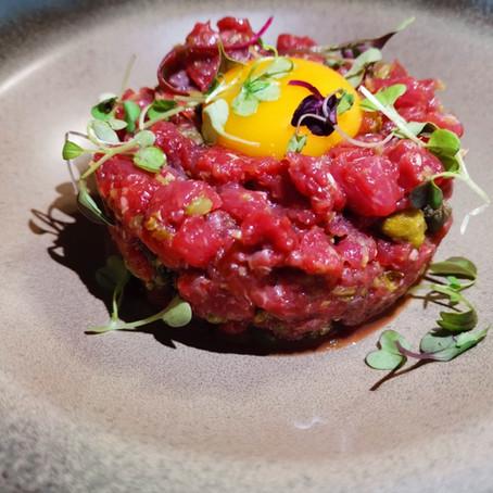 Steak tàrtar de vedella tallada al moment amb adobats, rovell d'ou i tabasco.