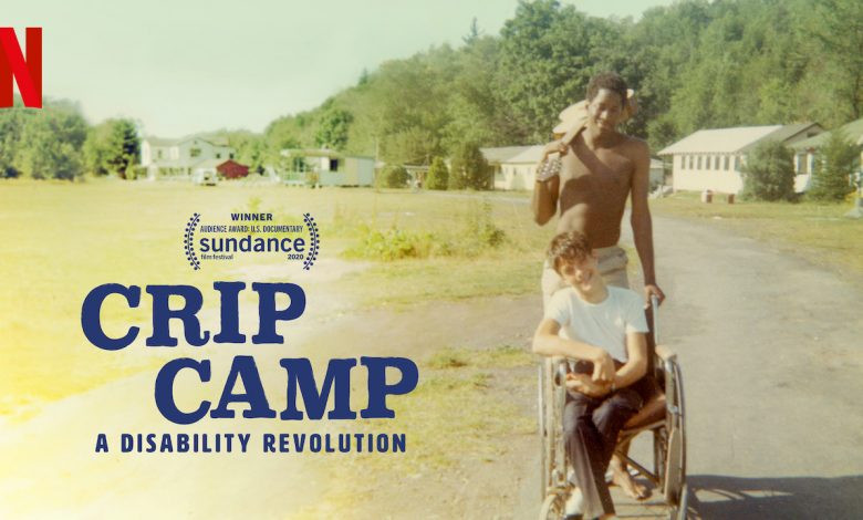Crip Camp. A Disability Revolution. Shows a phto from the 70s. A young man with no shirt and a guitar over his shoulder pushes a teenage boy in a wheelchair. They are both smiling with a background of cabins, grass and trees. In the corner is the Netflix logo, and a logo indicating it was the Winner of the Audience award at the Sundance Film festival.