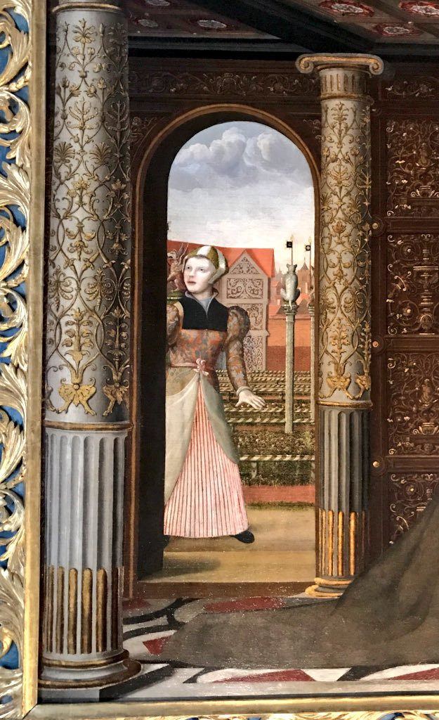 A young woman in a pink and brown dress peeks out from an intricately decorated archway.