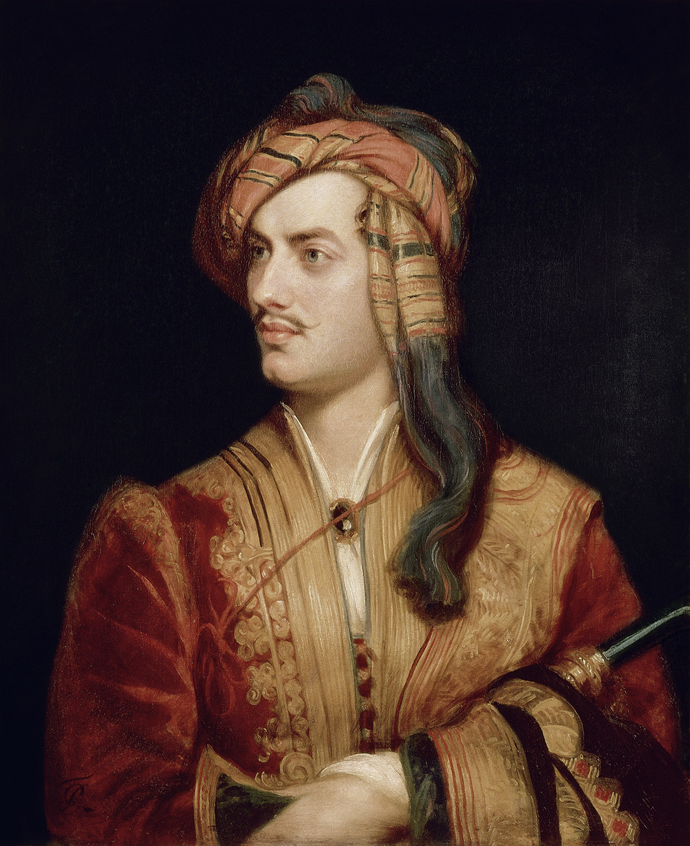 Lord Byron with a small mustache looks to the side. He is wearing a red jacket with gold trim, and a cold and red head wrap.