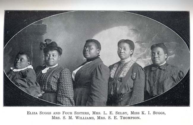 A black and white photograph of Eliza and her 4 sisters, all wearing smart church style clothes. Caption reads: ELIZA SUGGS AND FOUR SISTERS, MRS. L. E. SELBY, MISS K. I. SUGGS,  MRS. S. M. WILLIAMS, MRS. S. E. THOMPSON.