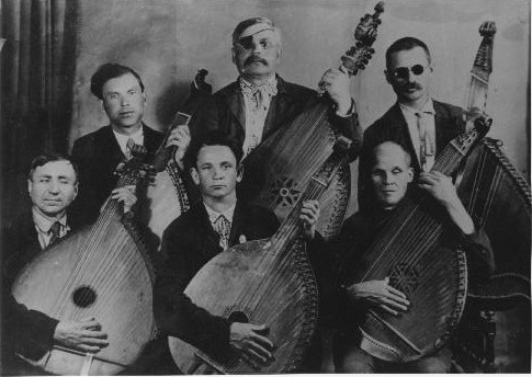 6 male bandura players in two rows, many are visibly blind or have dark glasses and eyepatches