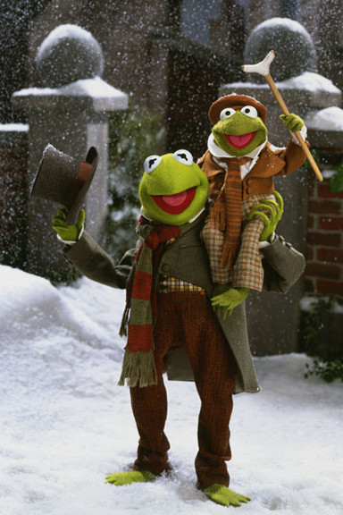 Kermit, a puppet frog, with a smaller puppet frog sitting on his shoulder and holding a crutch. Both are wearing old fashioned clothes and are in the snow.