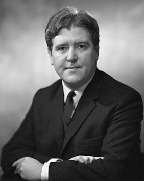 A black and white photo of a white man with dark hair in a suit.