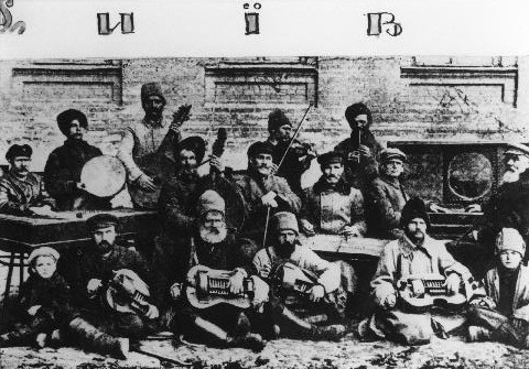 A group of men holding different types of lutes, hurdy gurdys and drums sit casually in old photo.