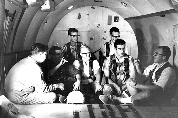 Black and white photo. 5 men sat in rows facing the front inside a cargo plane. Two additional men are sat facing them