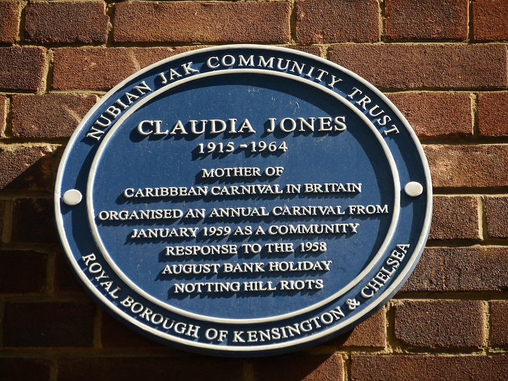 A circular blue plaque, around the outside reads: Claudia Jones 1915-1964 Mother of Caribbean Carnival in Britain. Organised an annual carnival from January 1959 as a community response to the 1958 August Bank Holiday Notting Hill riotsNubian Jak Community Trust, Royal Borough of ensington and Chelsea. Inside reads: