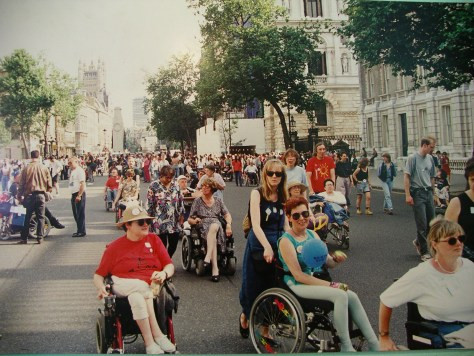 A photo of a street in London. Lots of people with various disabilities going along the road. They are all wearing very 90s fashion.