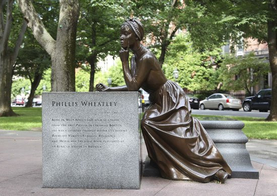 "A stone block with ""Phillis Wheatley"" and some of her story written on. A bronze Phillis statue leans against it, with one hand on her chin"
