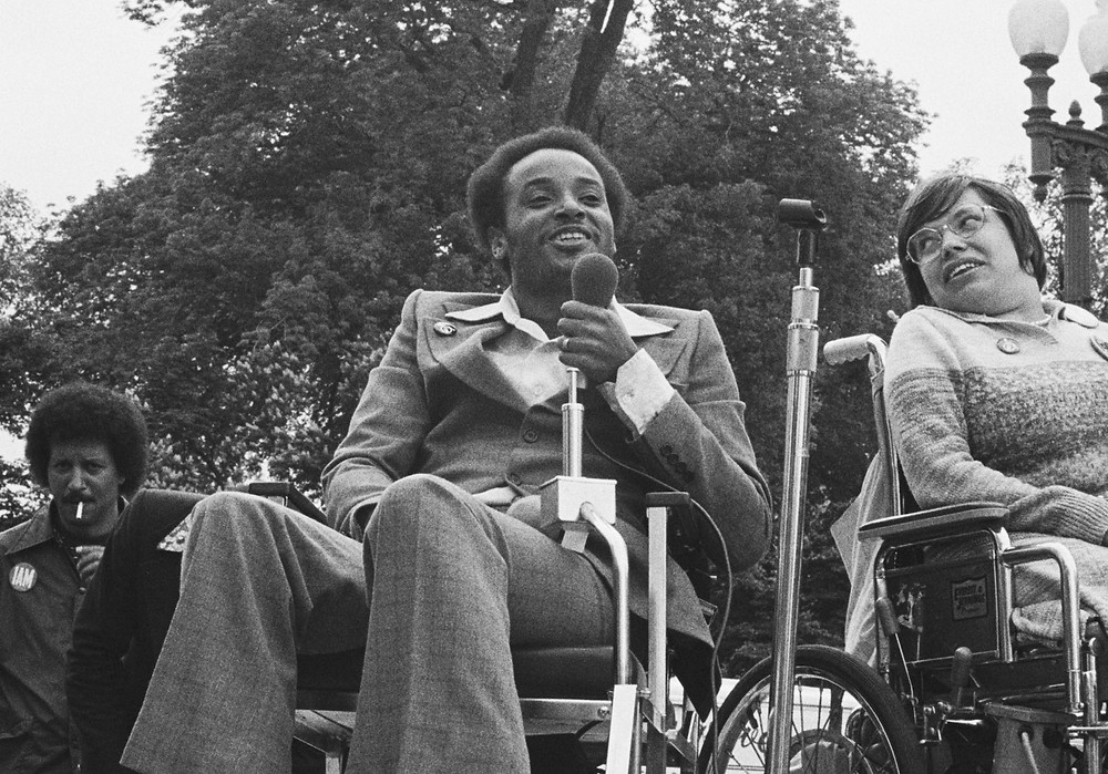 Black and white photo. A black man in a suit sits in his wheelchair holding a microphone to his mouth. On his right is a woman with glasses, also in a wheelchair facing slightly away from him and looking over her right shoulder at him