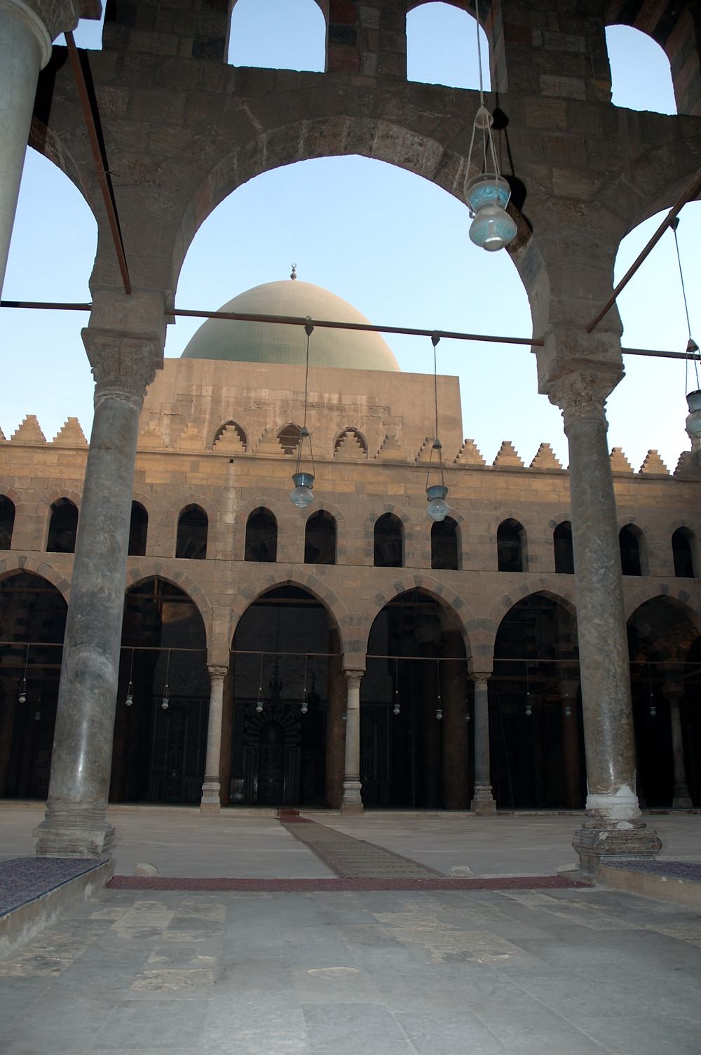 A mosque in morning light through an archway. The mosque has symmetrical arches, minarets and a dome, all in sand coloured stone.
