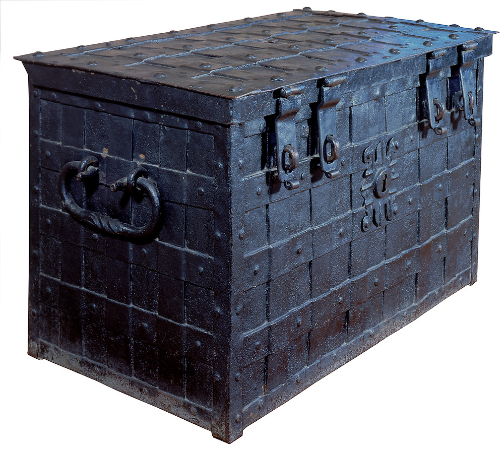 A large black metal rectangular chest, with large handles on either side and lots of detailing
