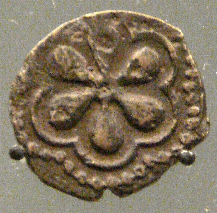 A bronze coloured metal coin with what looks like a 6 petal flower on it