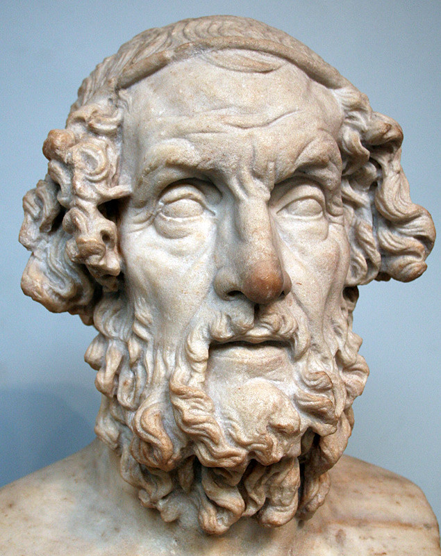 A white stone bust of a man with a long curly beard, balding but withcurly hair around the sides, and no detailing in the eyes.