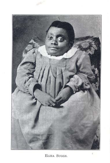 A black and white photograph of Eliza Suggs, a black woman of short stature. She is wearing an empire style dress with a frilly collar