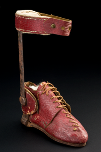A red lace up ankle boot, with a cuff attached by a metal splint.