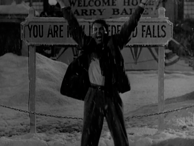 In black and white, a man holds his hands up in triumph in front of a street sign.
