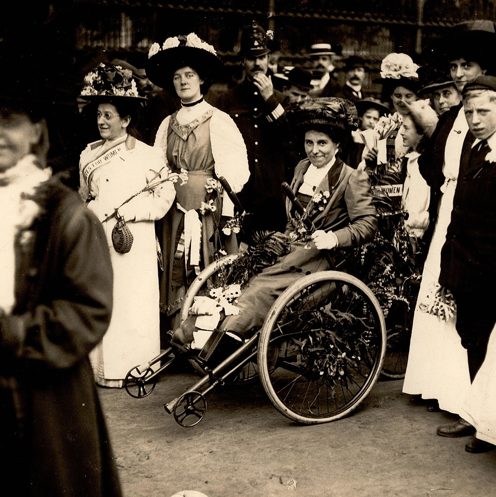 A woman with a big hat with flowers and a lot of pins and rosettes in a wheelchair smiles towards the camera. Around her are women with sahes, badges and remarkably big hats. Also behind them are police officers and men in straw boating hats. Black and white photograph.