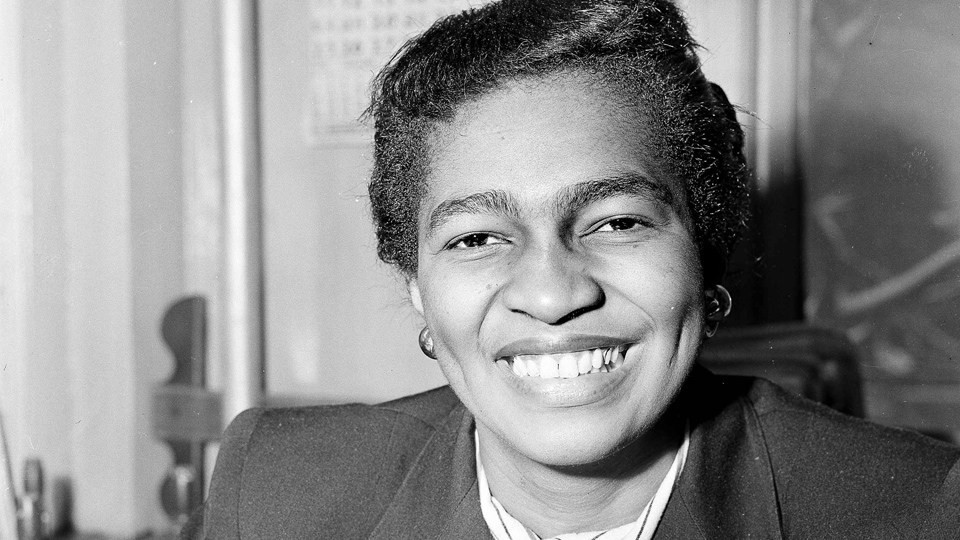 A black and white photo of Claudia Jones, a black woman, with her hair tied up. She is wearing a blazer and is smiling looking at the camera