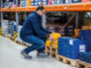 Ein Mann arbeitet in gehockter, ergonomischer Haltung im Logistikbereich. A man works in an ergonomic, crouched position in the logistics area.