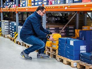 Ein Mann arbeitet in gehockter, ergonomischer Haltung im Logistikbereich. A man works in a crouched, ergonomic position in the logistics area. Un homme travaille dans une position ergonomique dans la zone logistique.