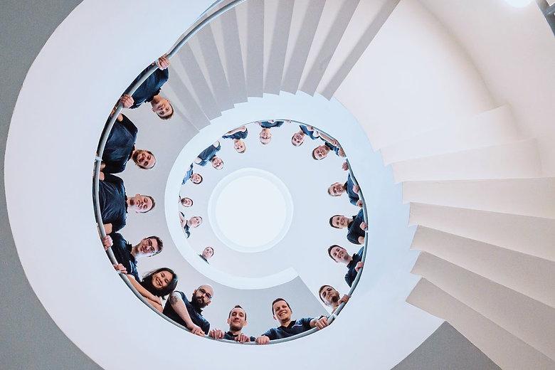 Das Team der MotionMiners auf der Spiraltreppe. Wir MotionMiners helfen Ihnen dabei Ihre Prozesse zu optimieren. MotionMiners team on the spiral staircase. We MotionMiners help you to optimize your processes automatically.