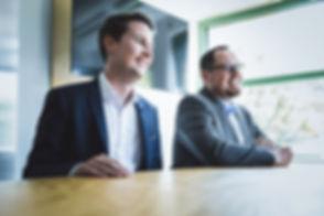 Zwei Businessmänner freuen sich über einen Dienstleistungsgespräch mit den MotionMiners für Prozessoptimierung. Two businessmen are happy about a service discussion with the MotionMiners for process optimization.