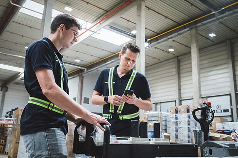 Zwei Mitarbeiter der MotionMiners nutzen Hardware wie Beacon, Smartphone und mobile Sensoren, um einen Logistikprozess automatisch zu messen und zu optimieren. Two MotionMiners employees use hardware such as beacons, smartphones and mobile sensors to automatically measure and optimize a logistics process.