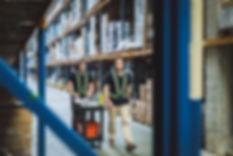 Zwei MotionMiners Mitarbeiter arbeiten in eine Lagerhalle im Logistikbereich, sie nutzen die Motion-Mining Technologie zur automatisierten Datenerfassung. Two MotionMiners employees work in a warehouse in the logistics area, they use motion mining technology for automated data acquisition.