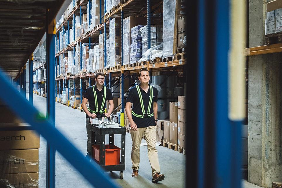 Zwei MotionMiners Mitarbeiter laufen mit Motion-Mining Technologie durch eine Lagerhalle