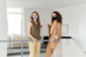 """Geschäftsfrauen mit Gesichtsmasken in der Corona Zeit nutzen die neue Technologie """"Motion-Mining Tracing Solution"""", um die Krankheit bei der Arbeit einzudämmen. Business women with face masks in the Corona period use the new technology """"Motion-Mining Tracing Solution"""" to contain the disease at work."""