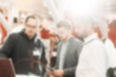 Drei Männer reden und diskutieren miteinander auf ein Event.