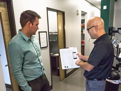 Reach technician discussing equipment checklist with dentist