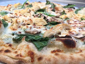 A close-up of a pizza topped with cheese, chicken, mushrooms, and spinach.