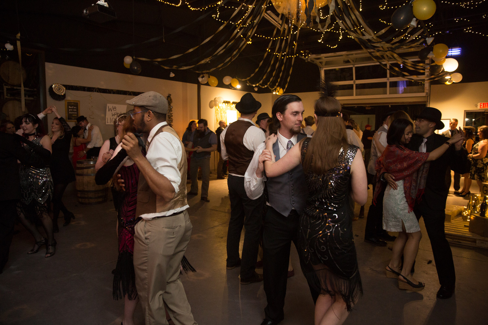 Couples swing dancing during a prohibition-themed party.