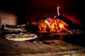 A picture of a pizza baking in a wood-fired oven.