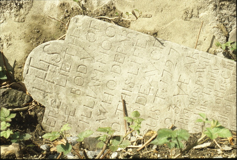 early 18th century headstone on its side (W. Moore 1727).  5/5/88