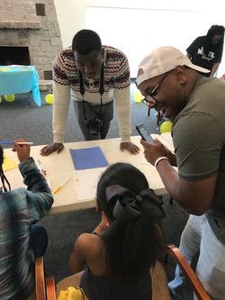 Two of our helpers helping a young girl with an acronym poem of her name