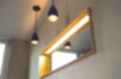 Fugenlose Wandgestaltung im Badezimmer, Spiegel mit Goldrahmen vor mineralischem Wandputz