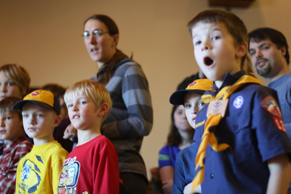 Excited Cub Scouts watch as their Pinewood Derby cars whiz by at Pinewood Derby 2015