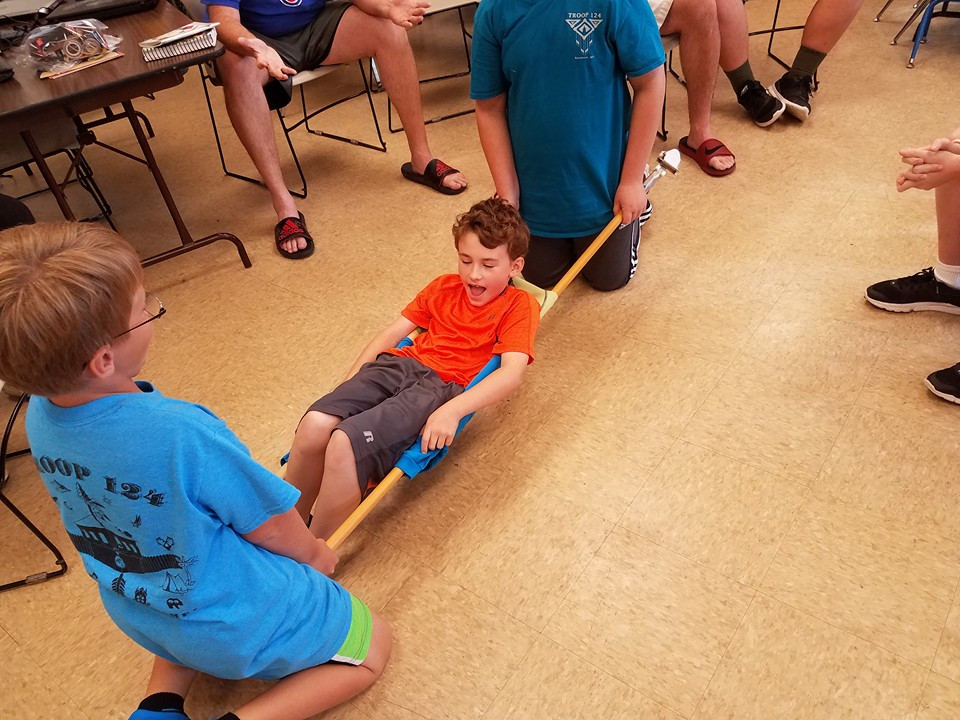 First year Boy Scout is lifted in a stetcher assembled from mop  handles and tshirts to help the boys understand how to carry a victim to safety.