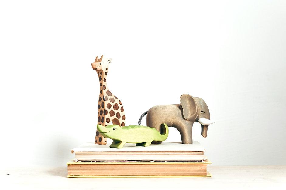 brown-and-green-giraffe-figurine-on-book