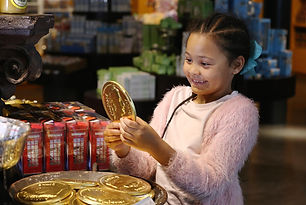 girl with gold chocolate coin in shop.jp
