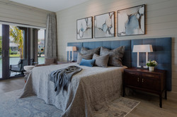 Conteporary primary bedroom with navy headboard